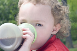 Young boy using sippy cup to drink beverage outdoors