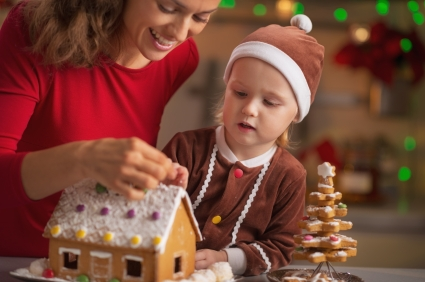 Happy mother and baby decorating christmas cookie house in kitchen