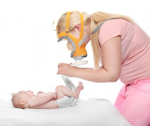 Diaper changing - hygiene concept. Young mother solving an smelly diaper accident.