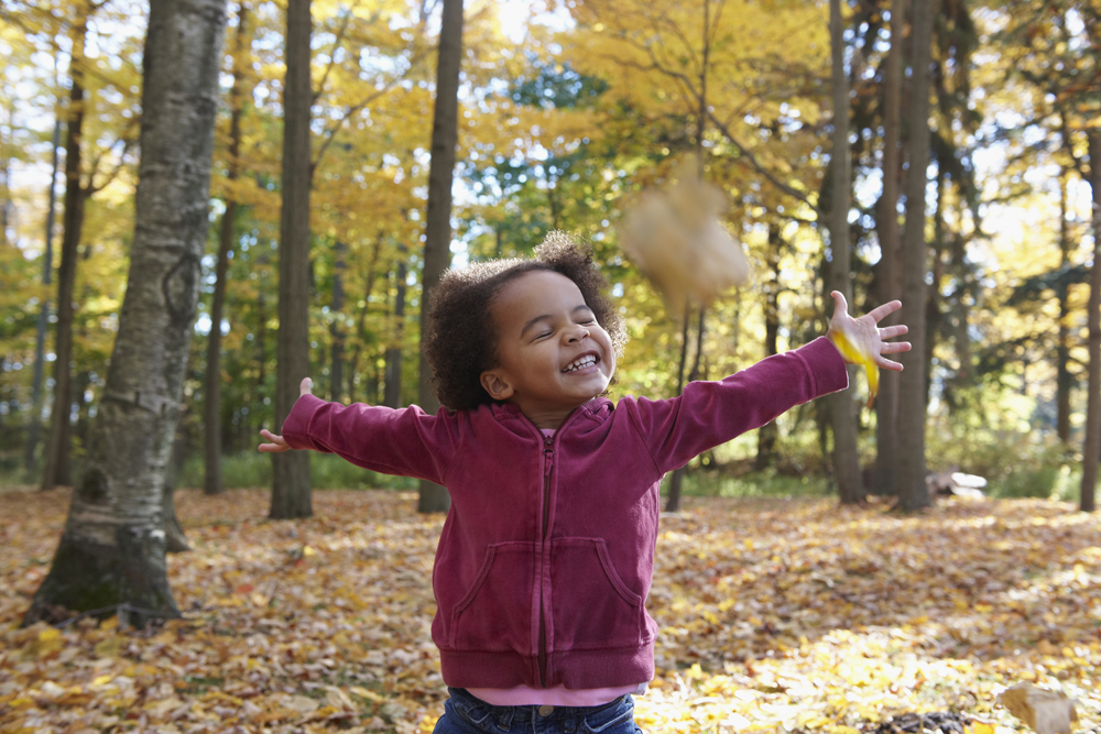 African American girl playing in autumn leaves