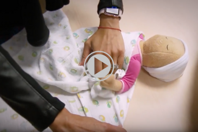 Dr. Jagruti Anadkat a newborn medicine specialist displays how to swaddle a newborn baby in a blanket